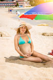 Pregnant woman relaxing on beach at hotel resort Stock Images