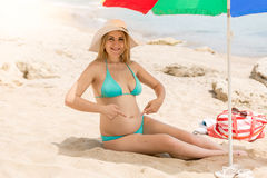 Pregnant woman relaxing and on beach and pointing at stomach Royalty Free Stock Photography
