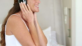 Pregnant woman relaxing on bed listening to music stock video