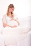 Pregnant woman relaxing on the couch Stock Photos