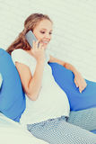 Pregnant woman relaxing on couch. Beautiful healthy pregnant woman relaxing on couch Stock Photo