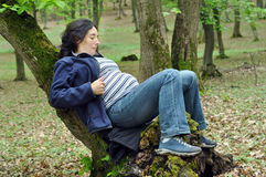 Pregnant woman relaxing in the forest Royalty Free Stock Image