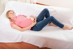 Pregnant woman relaxing at home on the couch Royalty Free Stock Photo