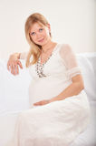 Pregnant woman relaxing at home on the couch Royalty Free Stock Images