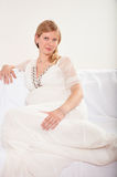 Pregnant woman relaxing at home on the couch Stock Photos