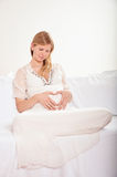 Pregnant woman relaxing at home on the couch Stock Photography