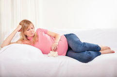 Pregnant woman relaxing at home on the couch Royalty Free Stock Photos