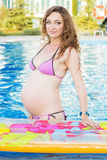 Pregnant woman relaxing near swimming pool Royalty Free Stock Image
