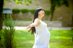 Pregnant woman relaxing in the park Stock Images
