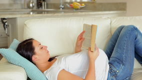 Pregnant woman relaxing and reading stock footage