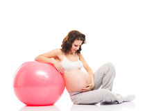 A pregnant woman relaxing with a red fitness ball Stock Photos