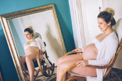 Pregnant woman relaxing at rocking chair Stock Photos