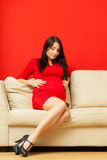 Pregnant woman relaxing on sofa touching her belly Stock Image