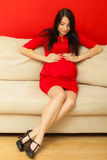 Pregnant woman relaxing on sofa touching her belly Royalty Free Stock Photo