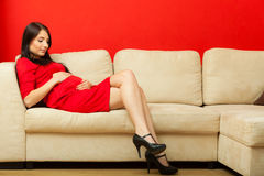 Pregnant woman relaxing on sofa touching her belly Stock Photos