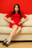 Pregnant woman relaxing on sofa touching her belly Royalty Free Stock Image