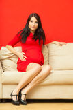 Pregnant woman relaxing on sofa touching her belly Royalty Free Stock Images