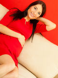 Pregnant woman relaxing on sofa touching her belly Royalty Free Stock Photography