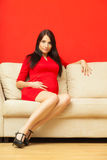 Pregnant woman relaxing on sofa touching her belly Stock Images