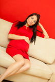 Pregnant woman relaxing on sofa touching her belly Stock Photo
