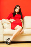 Pregnant woman relaxing on sofa touching her belly Royalty Free Stock Photos