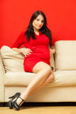 Pregnant woman relaxing on sofa touching her belly Stock Photography