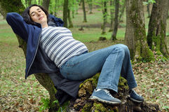 Pregnant woman relaxing on a tree Royalty Free Stock Images