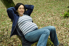 Pregnant woman relaxing on a tree Stock Images
