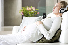 Pregnant Woman Relaxing Whilst Listening To Music On Headphones Stock Image