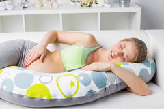 Pregnant woman resting on the couch with pillow Stock Images
