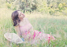 Pregnant woman is resting in the grass Royalty Free Stock Photos