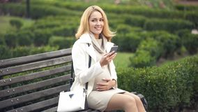 Pregnant woman resting on park bench using smartphone, stroking baby inside. Stock photo royalty free stock photos