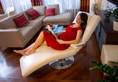 Pregnant woman resting on sofa. Pregnant woman reading book and laying down stock photography