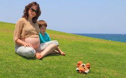 The pregnant woman rests with little son Royalty Free Stock Images