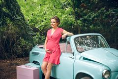 Pregnant woman and Retro car parked in old city street. royalty free stock photography