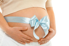 Pregnant woman with ribbon. Pregnant woman with blue ribbon over her belly. Hands on tummy. Side view, close up stock image
