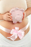 Pregnant woman with ribbon. Pregnant woman with pink ribbon. Holding pink piggy bank royalty free stock photo