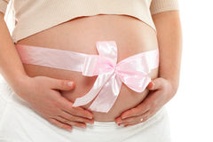 Pregnant woman with ribbon. Pregnant woman with pink ribbon over her belly. Hands on tummy. Frontal view, horizontal shot stock image