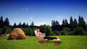 Pregnant woman in rocking chair on green meadow, stock footage Royalty Free Stock Photos