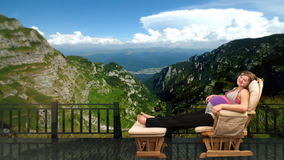 Pregnant woman on rocking chair at mountain, stock footage stock footage
