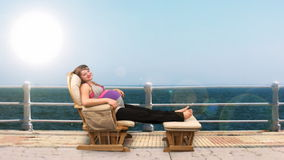Pregnant woman on rocking chair at seaside, stock footage Stock Photo