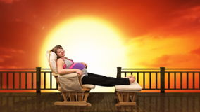 Pregnant woman on rocking chair at sunset, stock footage Stock Image