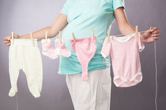 Pregnant woman with rope pins baby clothes Royalty Free Stock Image
