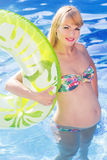 Pregnant woman with rubber ring in swimming pool Royalty Free Stock Image