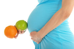 Pregnant woman's belly, apple and orange Royalty Free Stock Photography