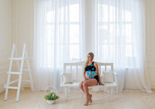 Pregnant woman's belly with blue butterflies over nursery background Royalty Free Stock Photography