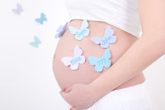 Pregnant woman's belly with colorful butterflies with male names Stock Image