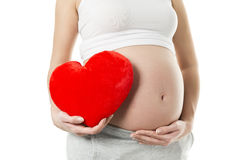 Pregnant woman's belly with heart shaped red pillow. Royalty Free Stock Photos