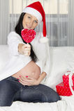 Pregnant woman in santa hat Stock Photography