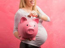 Pregnant woman saving money. And putting coin stock photos